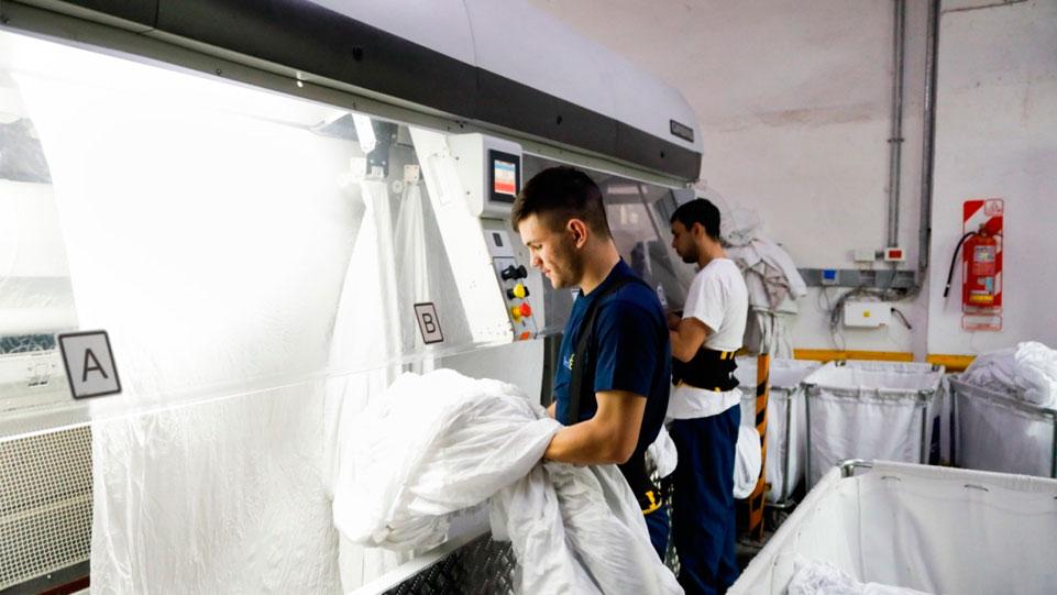 joven planchando en lavandería Industrial
